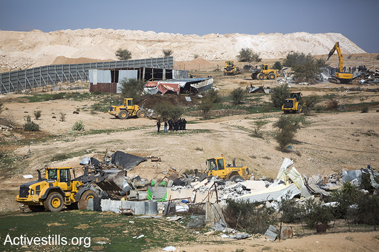 Seven tractors worked in tandem to demolish homes, animal sheds and other farm structures in Umm el-Hiran, January 18, 2017. (Keren Manor/Activestills)