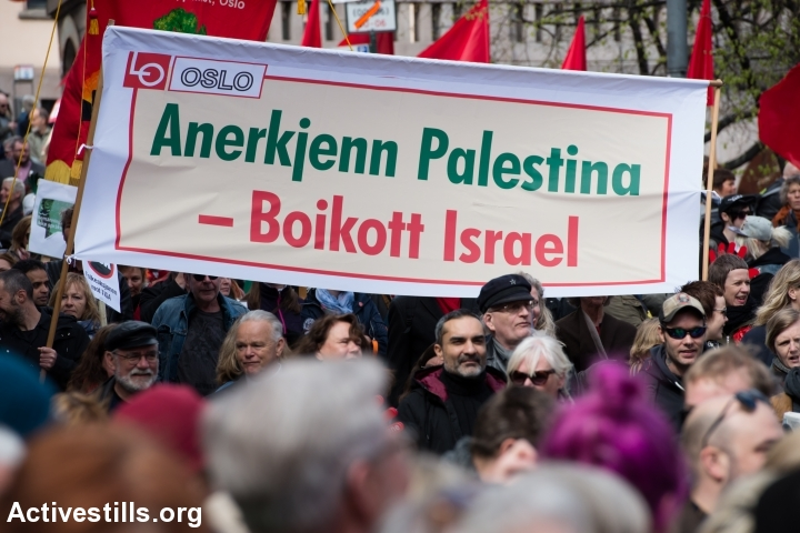 """A banner of the Norwegian Confederation of Trade Unions (LO) reads, """"Recognize Palestine, Boycott Israel"""" as thousands of Norwegians march through Oslo city streets in a May Day parade, May 1, 2016. (Ryan Rodrick Beiler/Activestills.org)"""