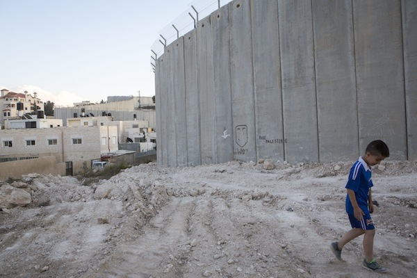 A young Palestinian boy walks by a section of the Palestinian side of the Separation Wall in the Jerusalem neighborhood of Abu Dis. September 29, 2014. (Photo by Miriam Alster/Flash90)