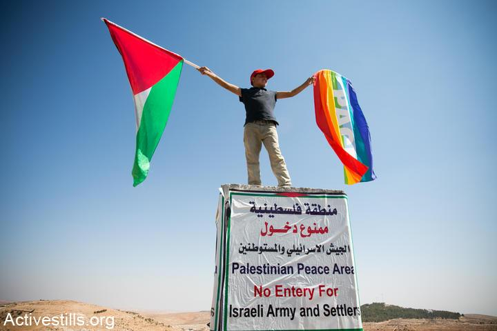 A Palestinian boy waves a peace flag and the Palestinian flag during a solidarity march with villages in the South Hebron Hills while he stands on a concrete block placed by the Israeli military to mark a firing zone, West Bank, September 22, 2012. (Yotam Ronen/Activestills.org)