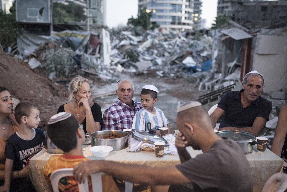 Three families hold an improvised, outdoor Shabbat dinner. Their homes were demolished following a years-long struggle against eviction without proper compensation, September 19, 2014. (Activestills.org)