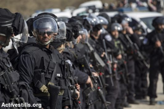 Israeli policemen stand guard as bulldozers demolish houses in the unrecognized Bedouin village of Umm el-Hiran, in the Negev desert, January 18, 2017. (Faiz Abu Rmeleh/Activestills.org)