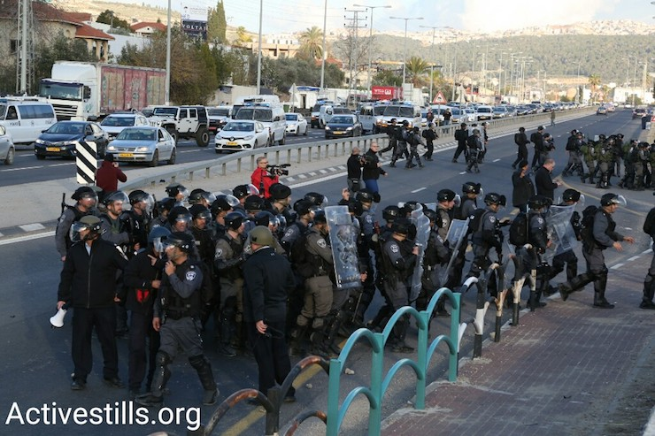 Israeli police wait for demonstrators marching to protest home demolitions, Ar'ara, January 21, 2017. (Keren Manor/Activestills)