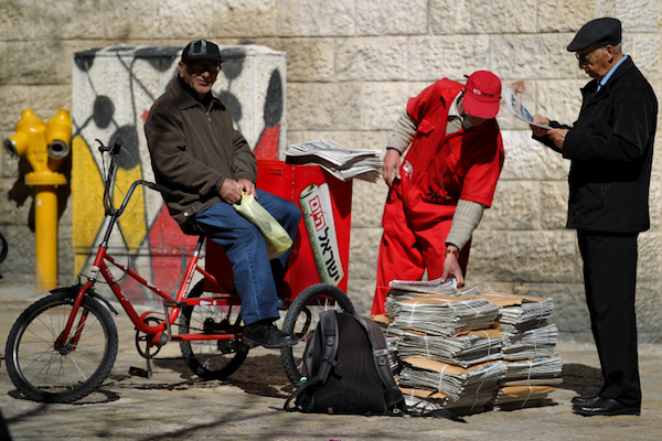 An 'Israel Hayom' employee hands out free copies of the daily newspaper in Jerusalem. (Nati Shohat/Flash90)
