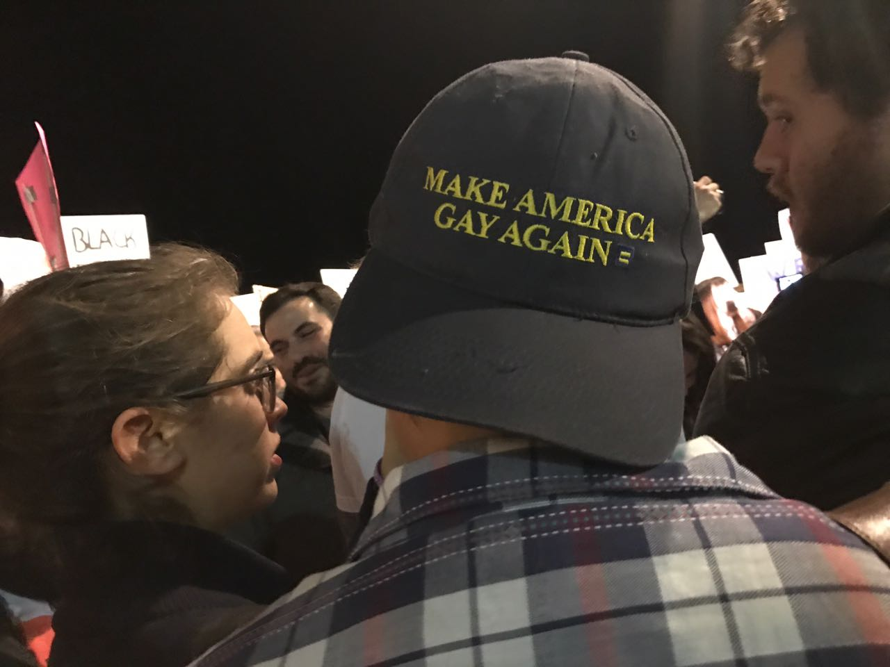 A man wearing a 'Make America Gay Again' hat takes part in the Women's March protest outside the U.S. embassy in Tel Aviv, January 21, 2017. (Tomer Neuberg/Flash90)