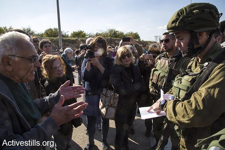 Soldiers prevent Israeli activists from passing through the Eliyahu checkpoint on their way to a joint Palestinian-Israeli nonviolent demonstration against land expropriation, January 7, 2017. (Keren Manor/Activestills.org)