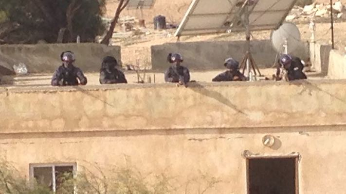 Israeli police positioned on a rooftop in Umm el-Hiran with their guns trained, January 18. 2017. (Isaac Kates Rose)