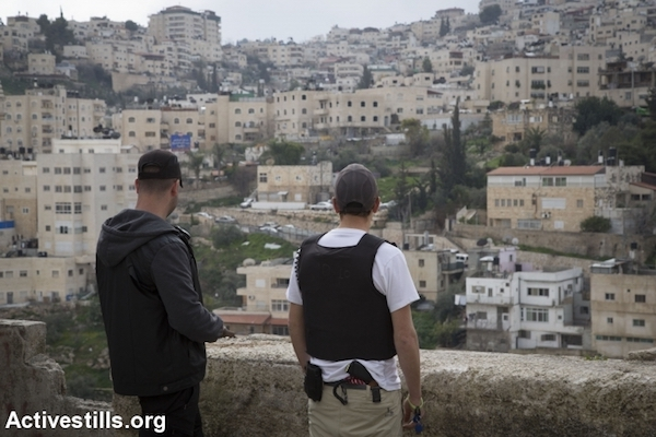 Private security guards stand atop a home taken over by Israeli settlers in the East Jerusalem neighborhood of Silwan, February 21, 2016. (Oren Ziv/Activestills.org)