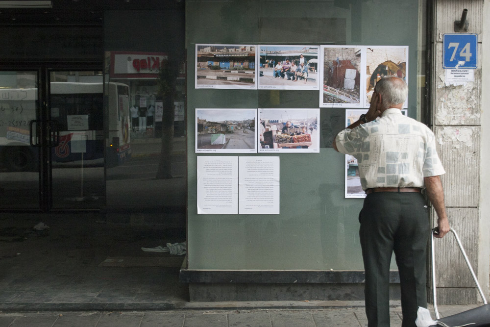 An Israeli man stops to look at an Activestills street exhibition in Tel Aviv, May 10, 2007. (Activestills.org)