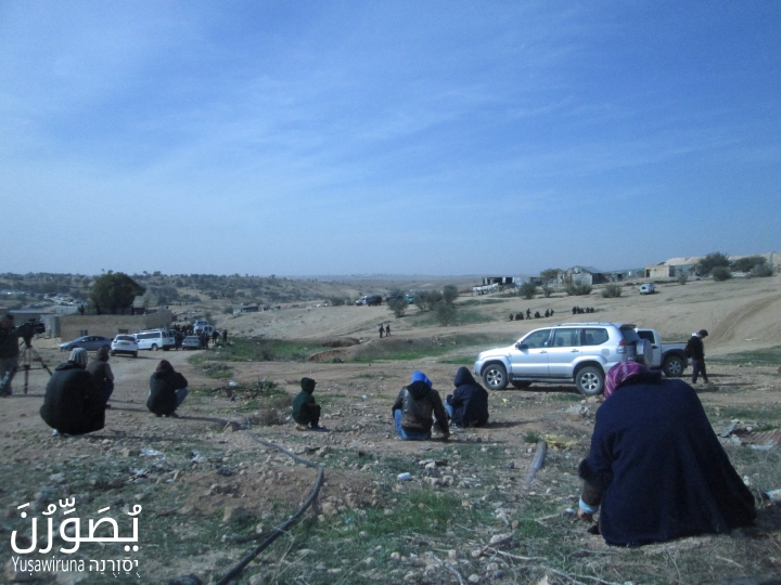 Residents of Umm el-Hiran sit on the ground opposite police, January 18, 2017. (Yuṣawiruna Project, Negev Coexistence Forum)