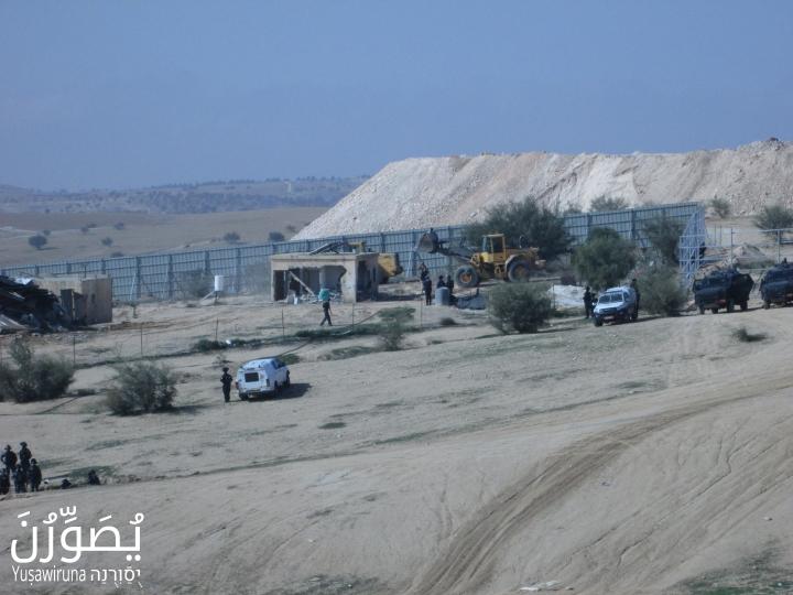 Bulldozers demolish a home in Umm el-Hiran as police stand guard, January 18, 2017. (Yuṣawiruna Project, Negev Coexistence Forum)
