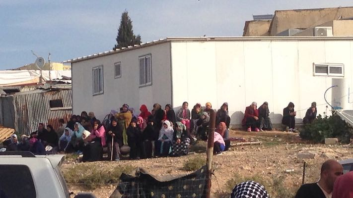Women from Umm el-Hiran surround a home slated for demolition in the village. (Isaac Kates Rose)