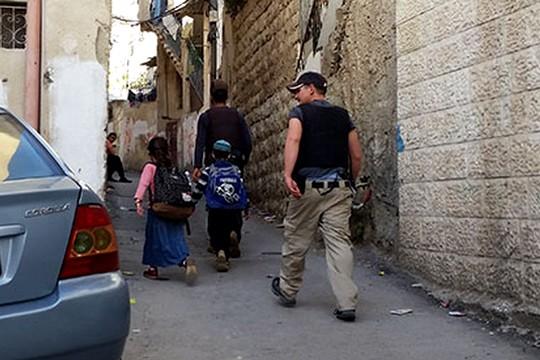 Security guards escort settler children in the neighborhood of Batan al-Hawa, East Jerusalem. December 2016. (Sarit Michaeli, B'Tselem)