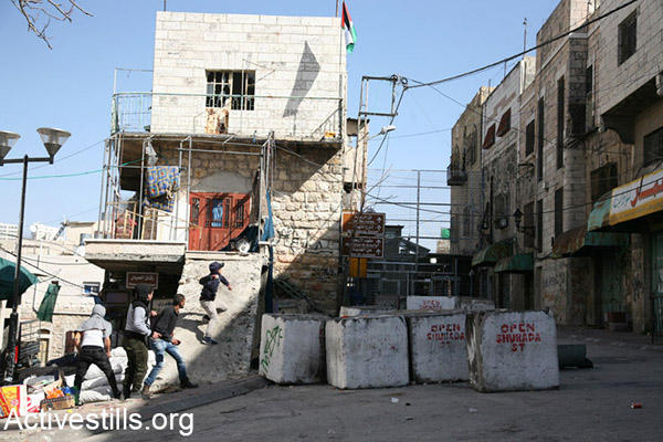 After Israeli troops broke up the protest with volleys of tear gas, a number of local youths stayed behind to respond to the soldiers by throwing stones, February 24, 2017. Hebron. (Haidi Motola/Activestills.org)