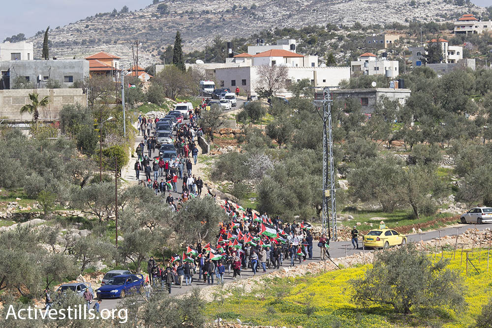 Demonstrators descend from the village of Bil'in to the Israeli wall, which is built on the village's agricultural land, February 17, 2017. (Oren Ziv/Activestills.org)