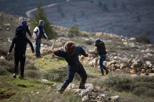 Young Jewish protesters throw rocks at Israeli police forces at the illegal outpost of Amona, February 1, 2017. (Hadas Parush/Flash90)