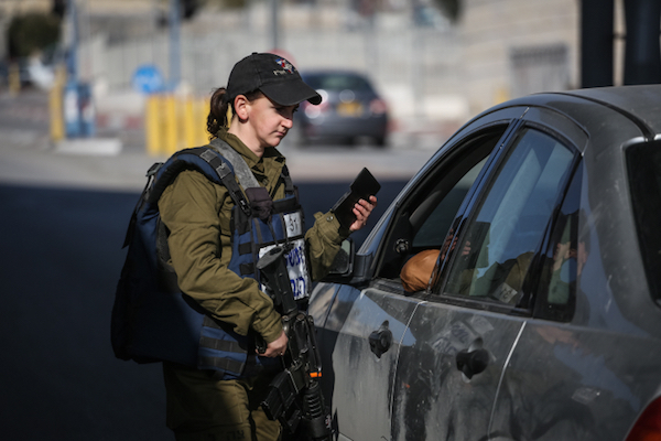 An Israeli military police officer checks IDs at the checkpoint at the entrance to Shuafat Refugee Camp in East Jerusalem, December 22, 2015. (Hadas Parush/Flash90)
