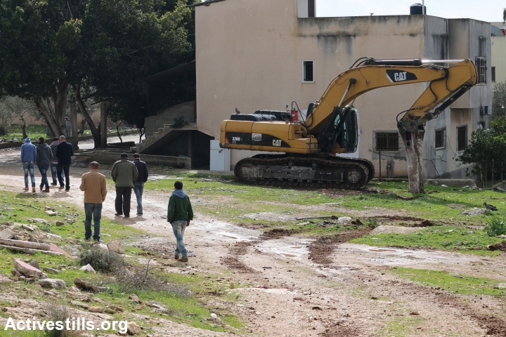 Palestinians walk beside a bulldozer that is forbidden by Israeli authorities to pave streets on private property, Shufa, West Bank, January 31, 2017. (Ahmad Al-Bazz/Activestills.org)