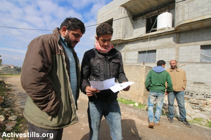 "Thaer Doroubi looks over a home demolition order issued by Israeli authorities for ""building without a permit"" in Area C, Shufa, near Tulkarem, West Bank, January 31, 2017. There are currently 12 Palestinian homes under the threat of demolition in the village. (Ahmad Al-Bazz/Activestills.org)"