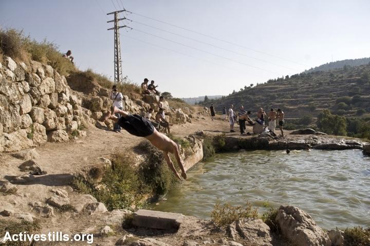 Israelis swim in a spring belonging to the destroyed Palestinian village of al-Walaja, near Jerusalem. (Anne Paq/Activestills.org)