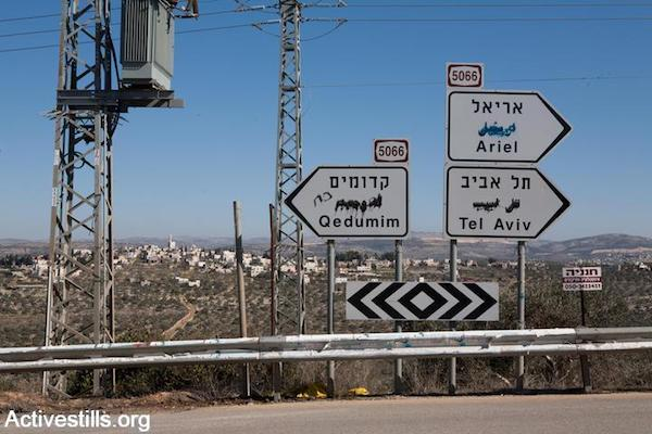 Road signs on which the Arabic writing has been deliberately defaced by settlers point towards the Israeli settlements of Ariel and Qedumim, Salfit District, West Bank, January 24, 2008. (Keren Manor/Activestills)