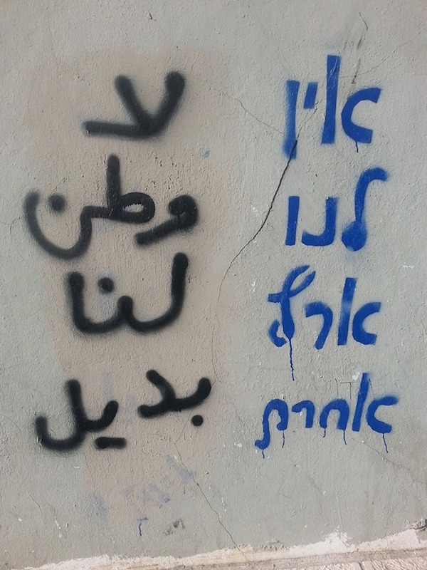 """Graffiti in Jaffa, which reads """"We have no other land"""" in Arabic and Hebrew, after the Arabic had been painted over and then restored. (Natasha Roth)"""
