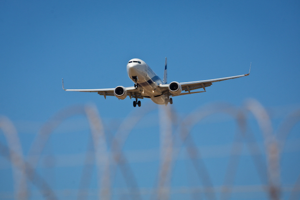 An El Al plane is seen through a barbed wire fence at Tel Aviv's Ben Gurion Airport. (Moshe Shai/Flash90)