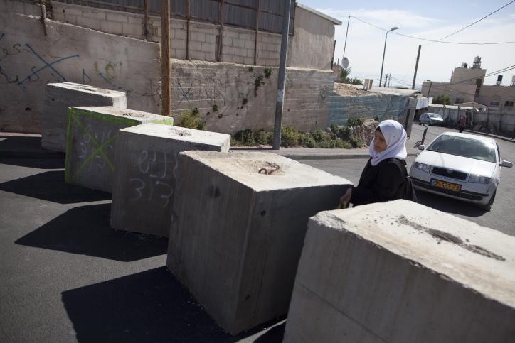 A Palestinian woman passes through concrete blocks that were installed by Israeli police in the East Jerusalem neighborhood of Jabal Mukaber, October 21, 2015. (Lior Mizrahi/Flash90)