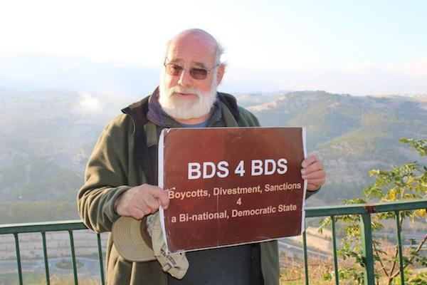 Jeff Halper holding a sign supporting the boycott, divestment and sanctions movement — not on the day he was detained by Israeli police. (Courtesy of Jeff Halper)