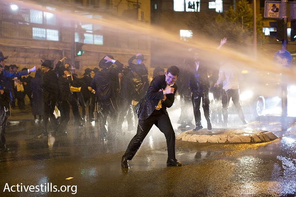 Ultra-Orthodox protesters are sprayed by a police water cannon during a demonstration in Jerusalem, March 23, 2017. (Oren Ziv/Activestills.org)