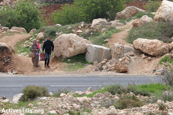 Palestinians walk around the large rocks and cinder blocks placed by the Israeli army to block the main entrance to Qalqas, south of Hebron, West Bank, March 17, 2017. (Ahmad al-Bazz/Activestills.org)
