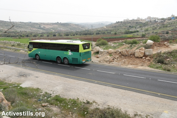 An Israeli bus that serves nearby settlements passes by the entrance to the village of Qalqas, which was closed off by the army during the Second Intifada and has yet to be opened, March 17, 2017. (Activestills.org)