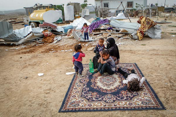 A Palestinian family sits in the remains of their demolished home in the West Bank village of Umm al-Kheir, April 6, 2016. (Wissam Hashlamon/Flash90)