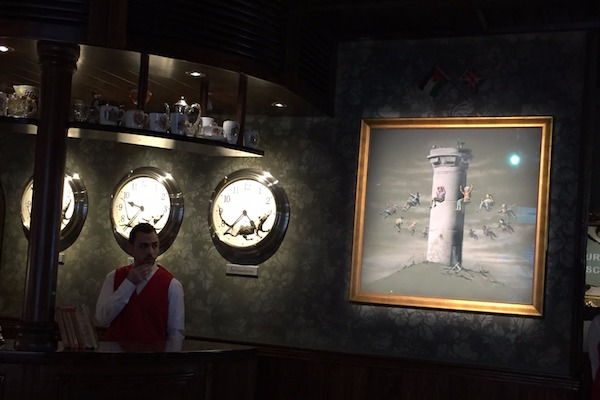 A member of staff next to a Banksy creation in The Walled Off Hotel, Bethlehem, March 3, 2017. (Haggai Matar)