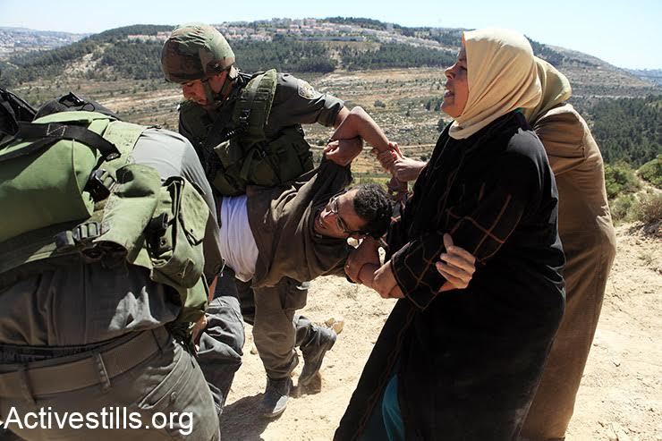 Basel al-Araj is seen being arrested by Israeli soldiers during a direct action against the construction of the separation wall in his village of Al-Walaja. Al-Araj a well known activist who participated in demonstrations and actions against the occupation, including in his village where demonstrations against the building of the wall began in 2006.