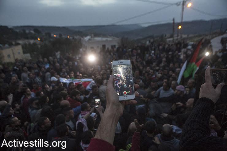 A Palestinian uses his smartphone to film the funeral of Basel al-Araj, Al Walaja, West Bank, March 16, 2017. (Activestills.org)