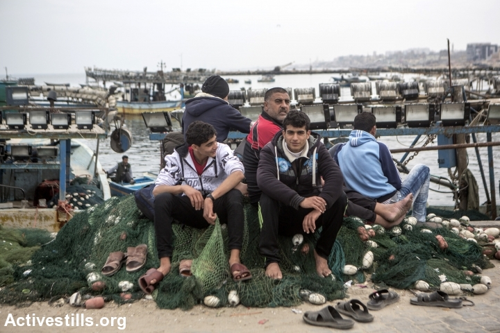 Fisherman sit on nets at the Gaza harbour, Gaza city, March 22, 2017. Israel unilaterally enforces a narrow maritime zone preventing fishermen from accessing areas they are entitled to according to previous peace agreements. The Israeli Navy routinely fires upon, arrests and confiscates the boats and equipment of fishermen even when they remain inside these limits. (Anne Paq/Activestills.org)