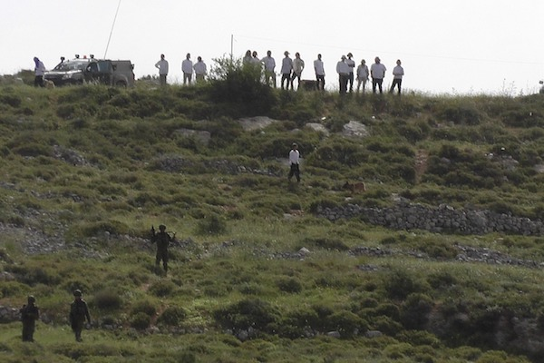 Settlers stand atop a hill near the Palestinian village of Urif, which was attacked twice on Saturday, April 22, 2017. (Urif Council)