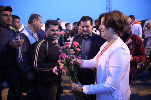 Hadash members and MKs hand out flowers to Palestinian laborers at the Eyal checkpoint. (Courtesy)