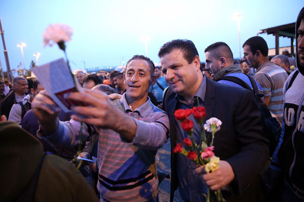 Hadash MK Ayman Odeh hands a workers' rights pamphlet and a flower to Palestinian laborers at the Eyal checkpoint. (Courtesy)