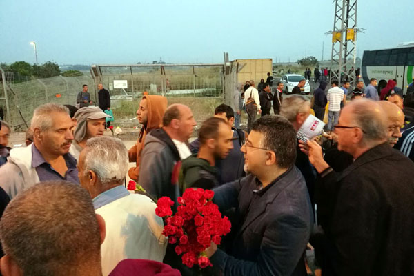 Hadash MK Yousef Jabareen hands out flowers to Palestinian laborers at the Eyal checkpoint. (Courtesy)
