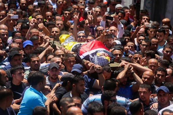 Mourners carry the body of Palestinian youth Mohammed al-Kasbeh, 17, during his funeral in Qalandiya refugee camp, near the West Bank city of Ramallah July 3, 2015. (Flash90)