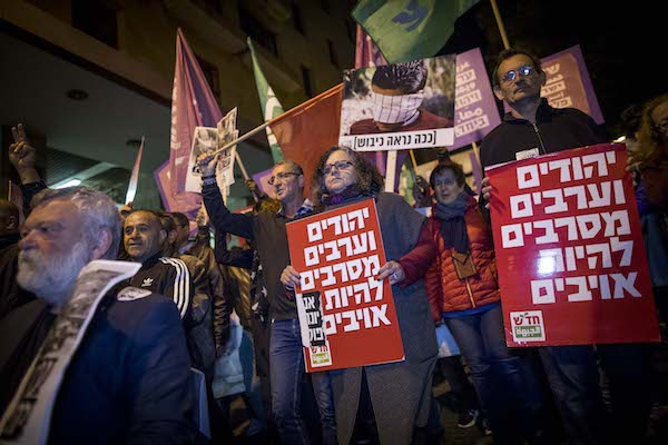 Palestinian and Israeli MKs, including Aida Touma-Suleiman and Dov Khenin of the Joint Arab List, hold signs at a protest against the occupation, Jerusalem, April 1, 2017. (Yonatan Sindel/Flash90)
