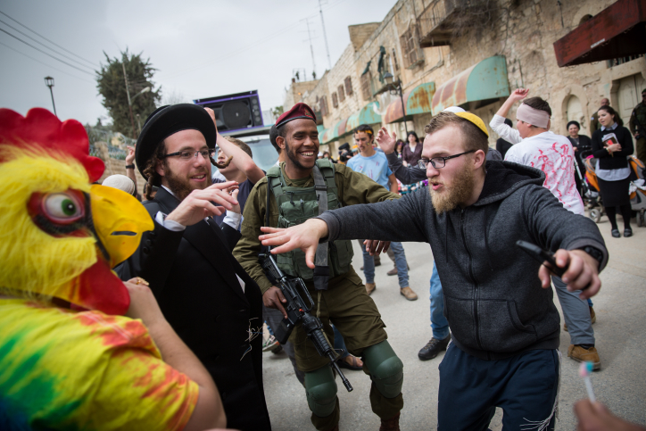 Jewish settlers wearing costumes dance with Israeli soldiers during the annual parade marking the Jewish holiday of Purim in the divided West Bank town of Hebron. March 12, 2017. Photo by Hadas Parush/Flash90)