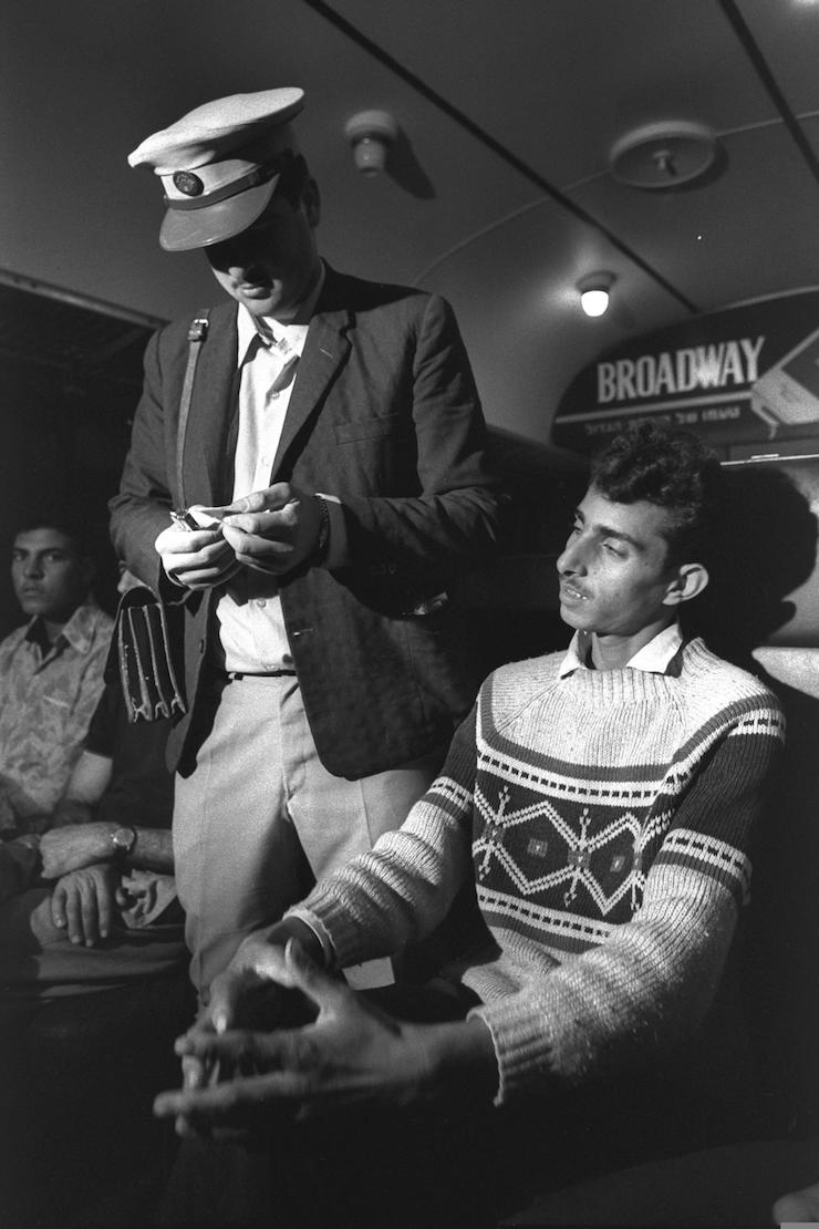 A conductor checks a Palestinian man's ticket on the first train from Gaza City to Tel Aviv, November 1, 1972. (Moshe Milner/GPO)