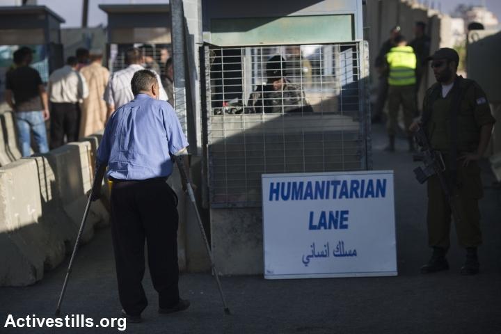 A disabled Palestinian man approaches a 'humanitarian lane' at the Israeli army's Qalandiya checkpoint separating Ramallah from Jerusalem during Ramadan, June 10, 2016. (Oren Ziv/Activestills.org)