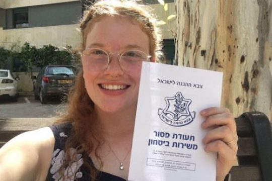 Conscientious objector Tamar Alon holds up her release papers after spending 130 days in military prison. (Courtesy of Mesarvot)