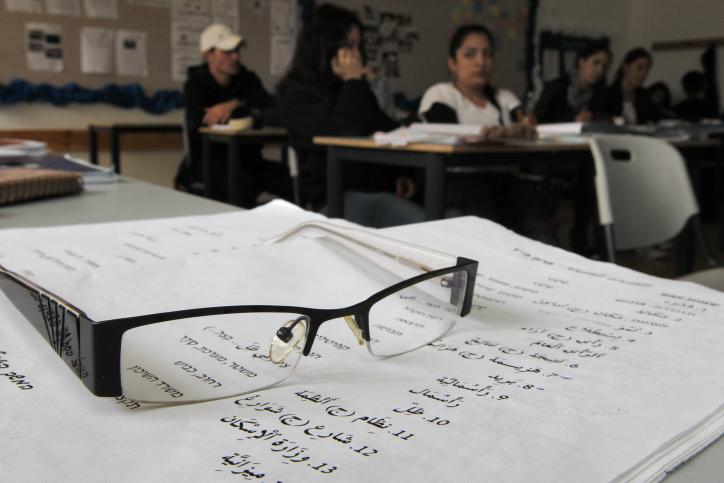 A pair of glasses resting on a worksheet used to teach Arabic to Israeli students, during an Arabic class at the Branco Weiss School. (Flash90)