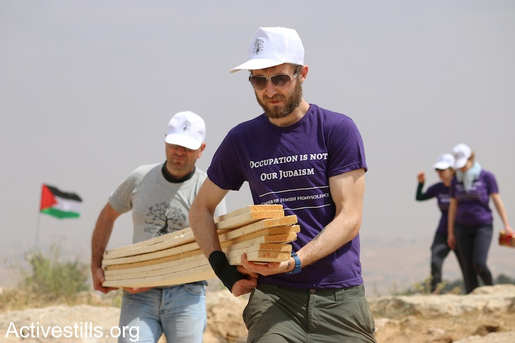 A Palestinian and an international Jewish activist carry wooden poles to build one of Sumud Freedom Camp's tents, Sarura, West Bank, May 19, 2017. (Ahmad al-Bazz/Activestills.org)