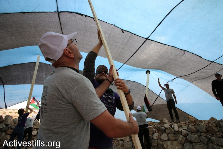A Palestinian and a diaspora Jewish activist set up wooden pole to build the Sumud Freedom Camp's main tent, Sarura, West Bank, May 19, 2017. (Ahmad al-Bazz/Activestills.org)